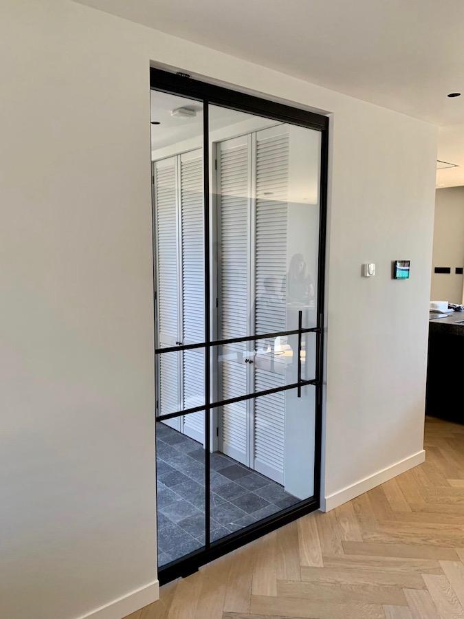 Brede glazen taatsdeur met staal in nieuwbouwwoning