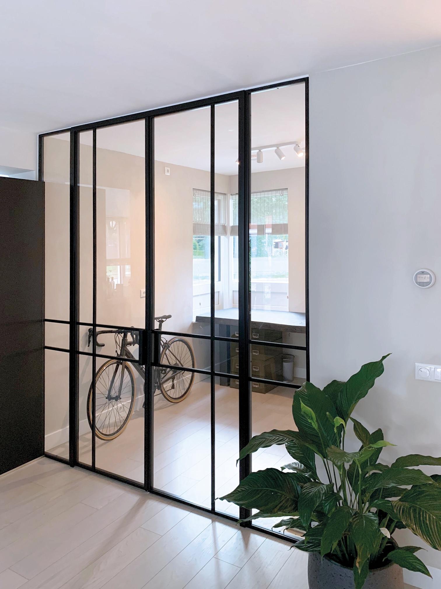 Stalen roomdivider met glas tussen woonkamer en kantoor